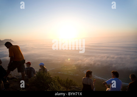 Hikers on top of Lions Head watching sunset above fog - in Cape Town on Summer Solstice 21 December - Stock Photo