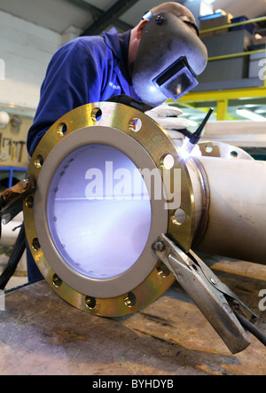 Welder at work on large pipe fabrication - Stock Photo