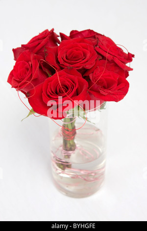 A bundle of red roses sit in water in a clear vase. - Stock Photo