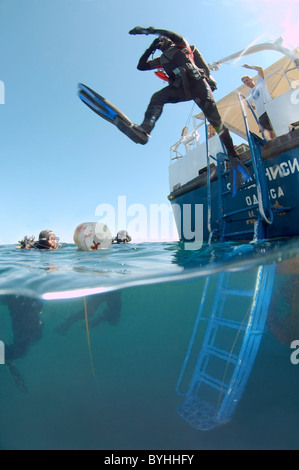 Underwater split level. Scuba diver jumps in water from the stern of a diving vessel - Stock Photo