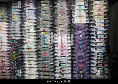 Mens shirts in cellophane wrapping on shelves in shop Wales UK - Stock Photo