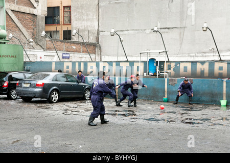 car wash workers play a game of pick up soccer on car wash lot Avenida Independencia Roma District Mexico City - Stock Photo