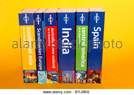 Studio shot of row of Lonely Planet guide books on a yellow background - Stock Photo