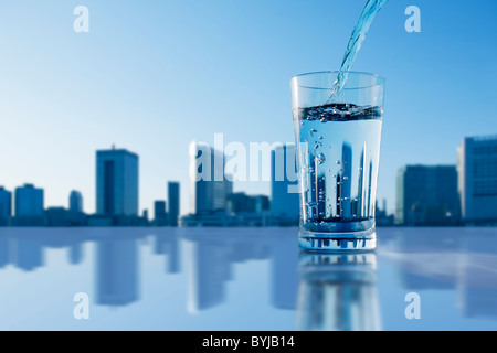 Glass Water Pouring Drink Skyline Urban Scene - Stock Photo
