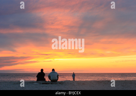 People watching the sunset at sea - Stock Photo