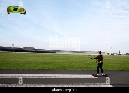 Kite skater on former runway at new city public Tempelhofer Park on site of famous former Tempelhof Airport in Berlin - Stock Photo