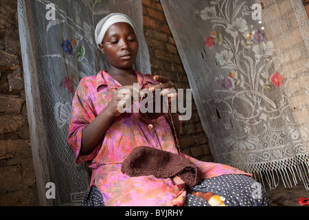 A woman knits clothes in rural Masaka, Uganda, East Africa. - Stock Photo