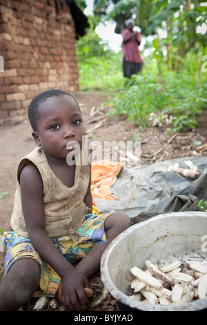 A young boy sits by a cooking pot full of bananas in rural Masaka, Uganda, East Africa. - Stock Photo