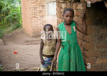 Two children stand outside their house in rural Masaka, Uganda, East Africa. - Stock Photo