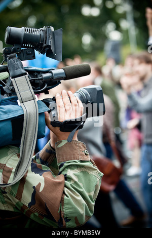News maker on reportage recording with camcorder - Stock Photo