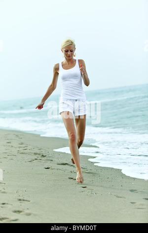 Happy young woman running on the beach - Stock Photo
