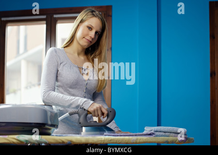 portrait of caucasian adult woman ironing clothes at home. Horizontal shape, front view, copy space - Stock Photo