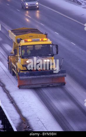 gritter spreading salt on the M1 motorway in winter snow near Leeds Yorkshire UK - Stock Photo