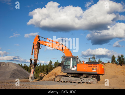 Hitachi ZAxis 350 lc excavator equipped with hydraulic rock breaker for rock quarry usage - Stock Photo