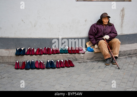 Elderly chinese man selling shoes on a cobbled street - Stock Photo