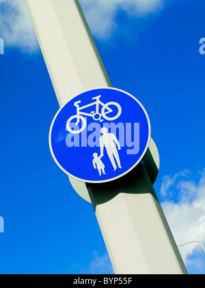 UK cycle and footpath sign on a lamp post with blue sky behind - Stock Photo