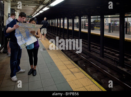 USA, New York, New York City, Young tourists look at map while waiting to board subway train in Manhattan - Stock Photo