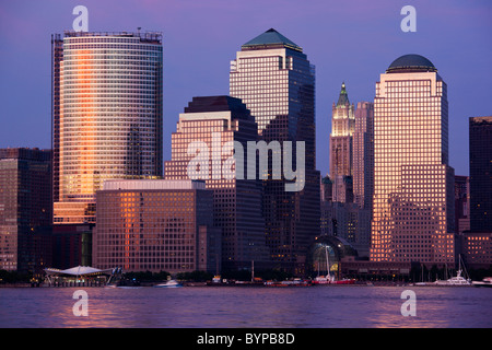 USA, New York, New York City, Setting sun reflects off building windows on Manhattan skyline, viewed from New Jersey - Stock Photo