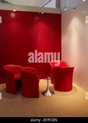 Red chairs and table situated in interior space with red and white walls, waiting area - Stock Photo