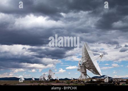 USA, New Mexico, Socorro, Radio telescopes in array under summer storm clouds at VLA Radio Observatory - Stock Photo