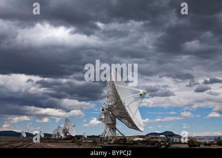 USA, New Mexico, Socorro, Radio telescopes under summer storm clouds at VLA Radio Observatory - Stock Photo