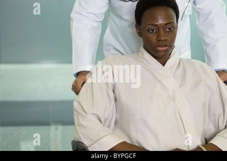Female patient being pushed in wheelchair - Stock Photo