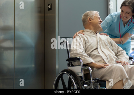 Nurse helping patient in wheelchair - Stock Photo