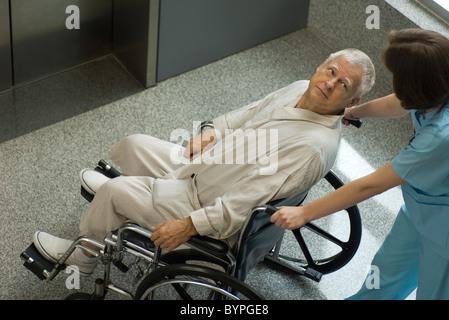 Nurse pushing senior patient in wheelchair - Stock Photo
