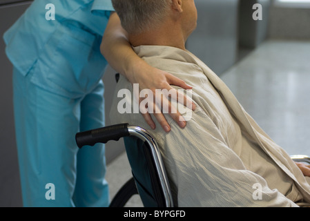 Nurse helping patient in wheelchair, cropped - Stock Photo