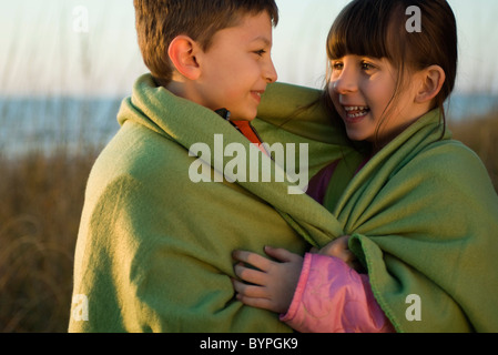 Children wrapped together in blanket outdoors, portrait - Stock Photo