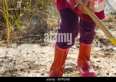 Child working outdoors with gardening tool - Stock Photo