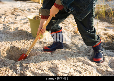 Boy digging hole in sand - Stock Photo