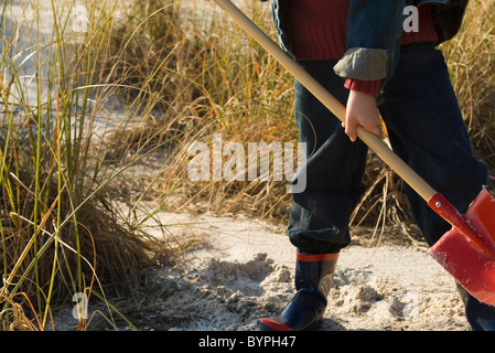 Boy digging with shovel in sand - Stock Photo