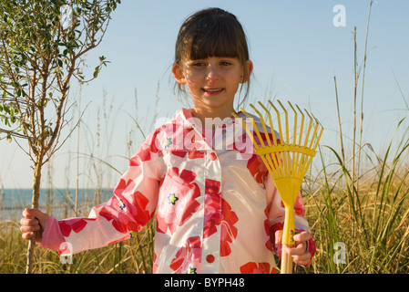 Young girl with gardening rake standing next to tree sapling Stock Photo
