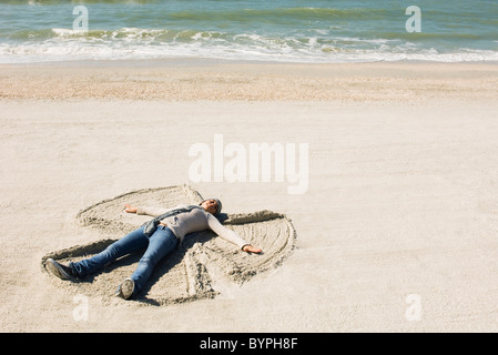 Preteen girl at beach making snow angel in sand - Stock Photo