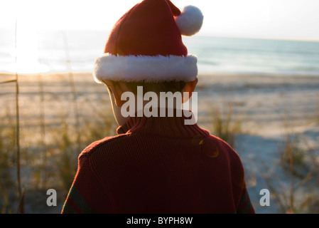 Boy exploring outdoors wearing Santa hat, beach in background - Stock Photo