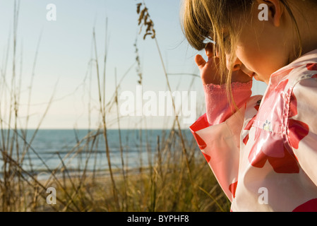 Young girl outdoors, sea in background - Stock Photo