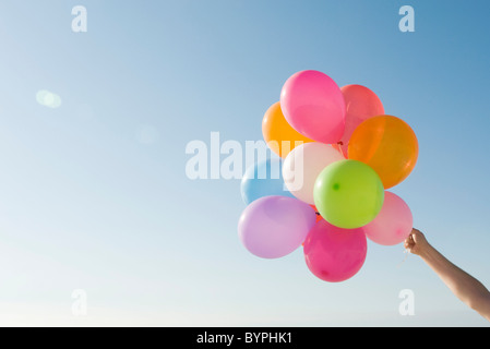 Bunch of helium balloons held aloft against clear blue sky - Stock Photo
