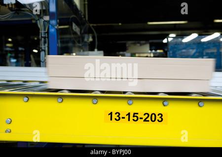Cardboard box moving along conveyor belt in carpet tile factory - Stock Photo