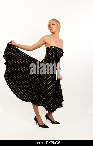 young woman with short cropped silver hair in a fifties style strapless dress - Stock Photo