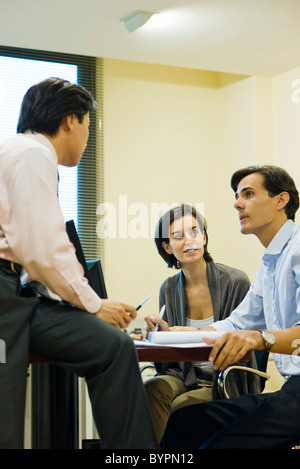 Executives talking together at desk - Stock Photo