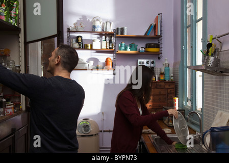 Couple in kitchen together, wife doing dishes, husband opening pantry - Stock Photo