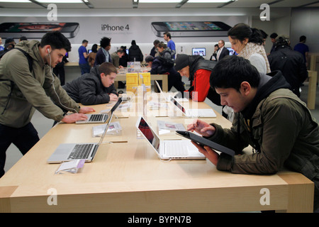 UK. CUSTOMERS TRYING NEW LAPTOPS AT AN APPLE MACINTOSH STORE IN LONDON - Stock Photo