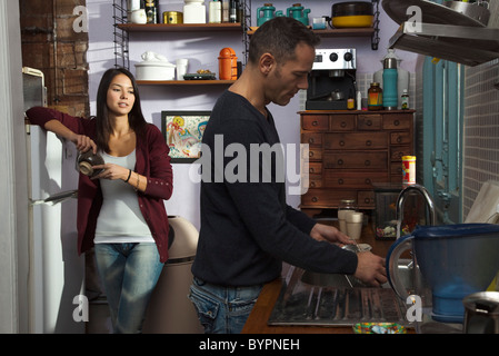 Couple in kitchen, husband doing dishes - Stock Photo