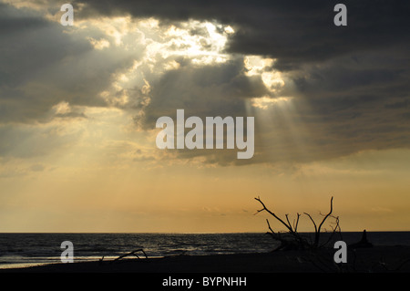 Sun breaking through clouds on the beach at Tarcoles, Costa Rica. - Stock Photo