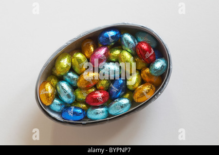 Lindt miniature easter eggs in coloured foil wrappers in easter egg half container - Stock Photo