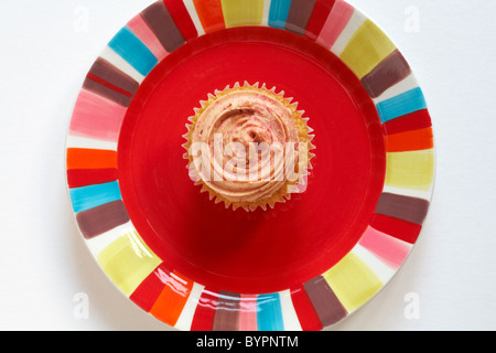 looking down on Marks & Spencer strawberry and vanilla cupcake on brightly coloured red plate - from above - Stock Photo