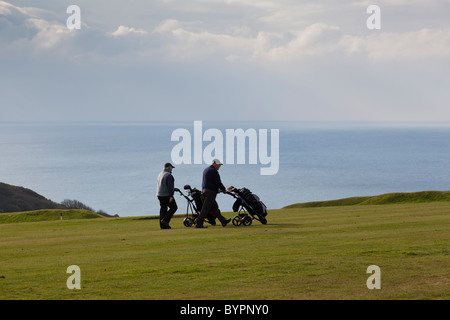 Golfers walk along the fairway, Whitsand Bay golf club, with the sea providing a stunning backdrop, Crafthole, Cornwall, - Stock Photo
