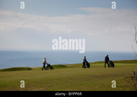 Golfers walk along the fairway Whitsand Bay golf club, with the sea providing a stunning backdrop, Crafthole, Cornwall, - Stock Photo