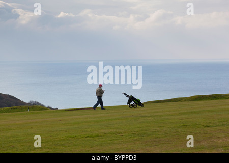 Golfer walks along the fairway, Whitsand Bay golf club, with the sea providing a stunning backdrop, Crafthole, Cornwall, - Stock Photo